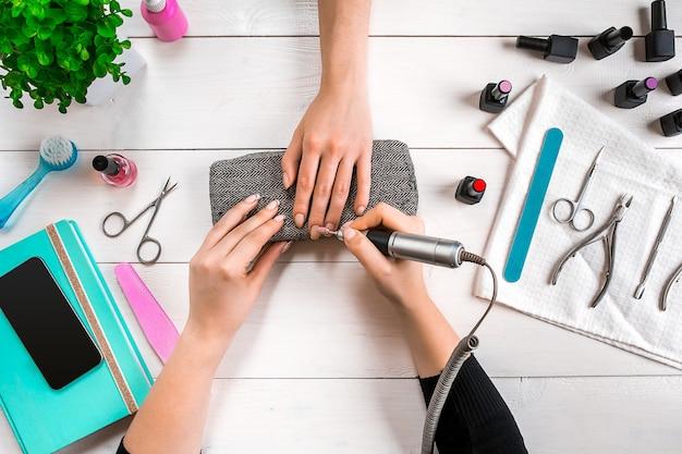 Nagelverzorging. close-up van vrouwelijke handen die nagels met professionele nagelvijl indienen in de schoonheidssalon van de nagel. bovenaanzicht