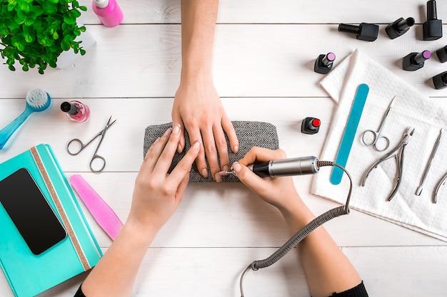 Nagelverzorging. close-up van vrouwelijke handen die nagels met professionele nagelvijl indienen in de schoonheidssalon van de nagel. close-up van de handen van de schoonheidsspecialiste die perfecte manicure op de handen van de vrouw doen. nagel hygiëne. bovenaanzicht