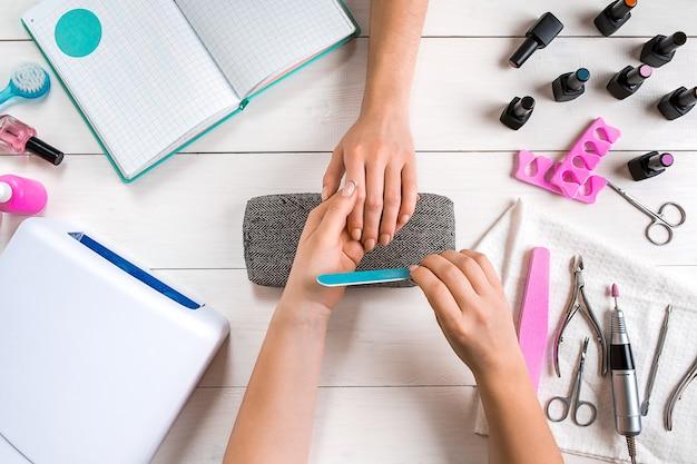 Nagelverzorging close-up van vrouwelijke handen die nagels vijlen met professionele nagelvijl in beauty nagelsalon top ...