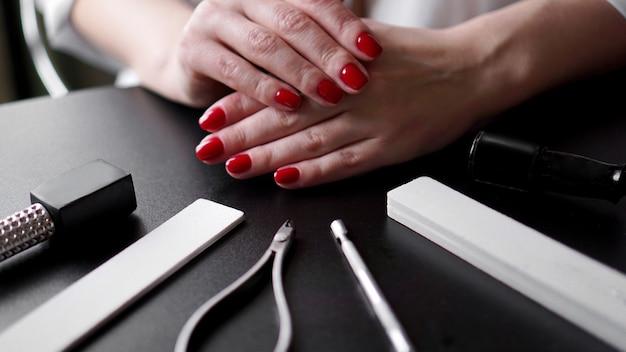 Nagelverzorging. perfecte nagels geschilderd met rode nagellak op zwarte achtergrond. professionele manicuregereedschappen. schoonheid auto