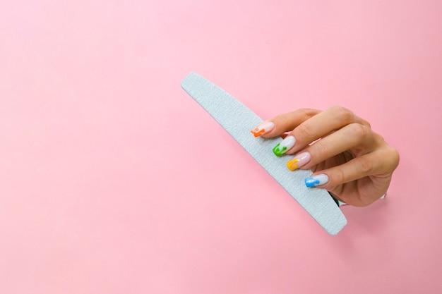 Nagelvijl in de hand van een jonge vrouw op een roze achtergrond uit het gat. kopieer ruimte