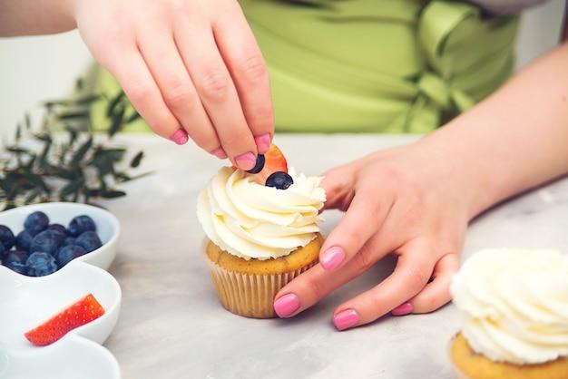 Nagerechten. banketbakker versieren cupcakes met roomkaas, close-up. banketbakker versieren cupcake met bosbes.