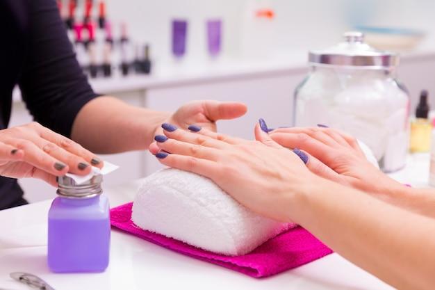 Nails salon vrouw nagellak verwijderen met weefsel