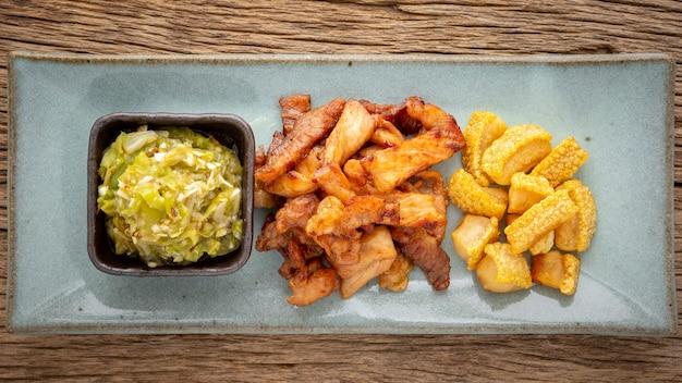 Nam prik num, thais eten, noord-thaise groene chilli dip met gebakken varkensvlees en knapperig varkensvlees geknetter in rechthoekige keramische plaat op rustieke natuurlijke houtstructuur achtergrond, bovenaanzicht