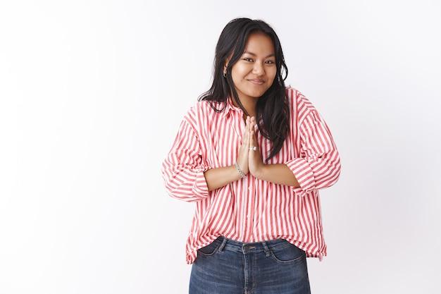 Namasté geniet van uw verblijf. portret van schattig aangenaam en gelukkig jong aardig vietnamees meisje in gestreepte blouse palmen tegen elkaar drukken in aziatische groet gebaar glimlachend in de camera vrolijk over witte muur