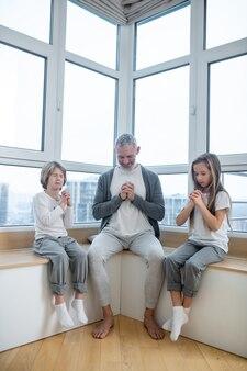 Namasté. grijsharige man en zijn kinderen zitten vredig met namaste