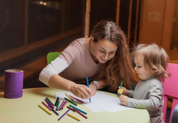 Nanny leert een klein meisje tekenen met kleurpotloden terwijl ze aan een tafel in een kinderentertainmentcentrum zit
