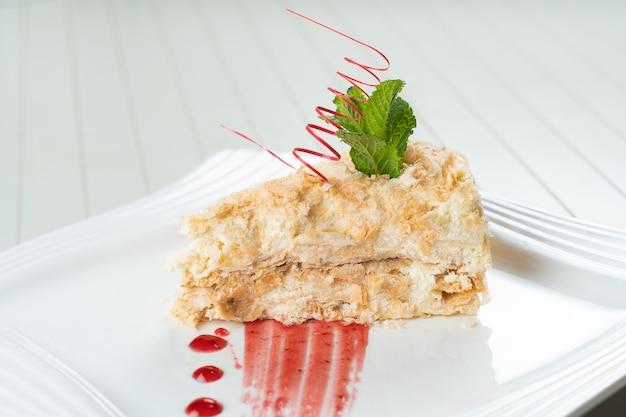 Napoleon cake versierd met een spiraal van rode chocolade, munt en bessenjam op een witte plaat. gelaagde cake met banketbakkersroom.