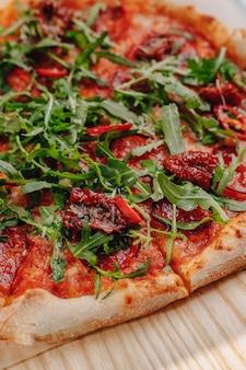 Napolitaanse pittige pizza met ham, kaas, rucola, basilicum, tomaten, peperoni-peper besproeid met kaas op een houten bord op een tafelkleed in een cel met een plek voor tekst