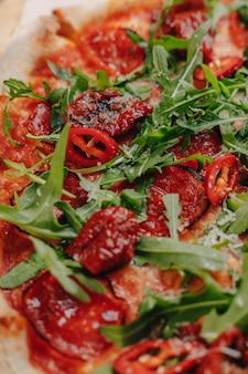 Napolitaanse pittige pizza met ham, kaas, rucola, basilicum, tomaten, peperoni-peper besproeid met kaas