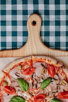 Napolitaanse pizza met champignons, kaas, rucola, basilicum, tomaten besprenkeld met kaas op een houten bord op een tafelkleed in een cel met een plek voor de tekst