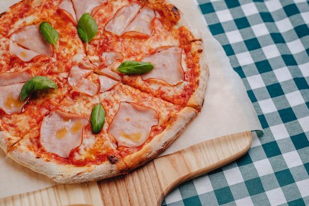Napolitaanse pizza met ham, kaas, rucola, basilicum, tomaten besprenkeld met kaas op een houten bord op een tafelkleed in een cel