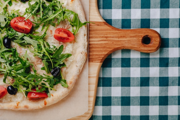 Napolitaanse pizza met tonijn, kaas, rucola, basilicum, tomaten, olijven, bestrooid met kaas.