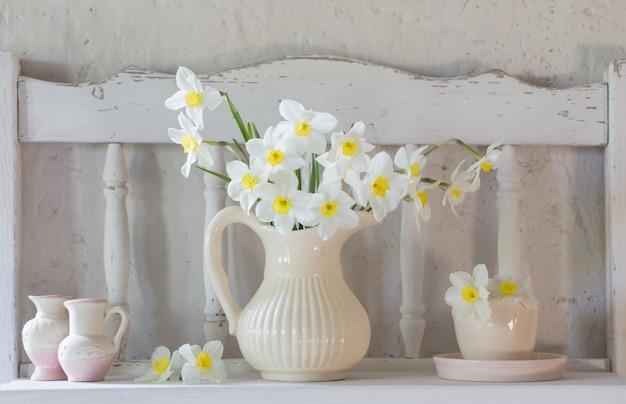Narcissen in kruik op witte tafel