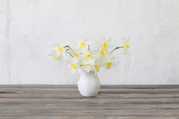 Narcissus in vaas op houten tafel