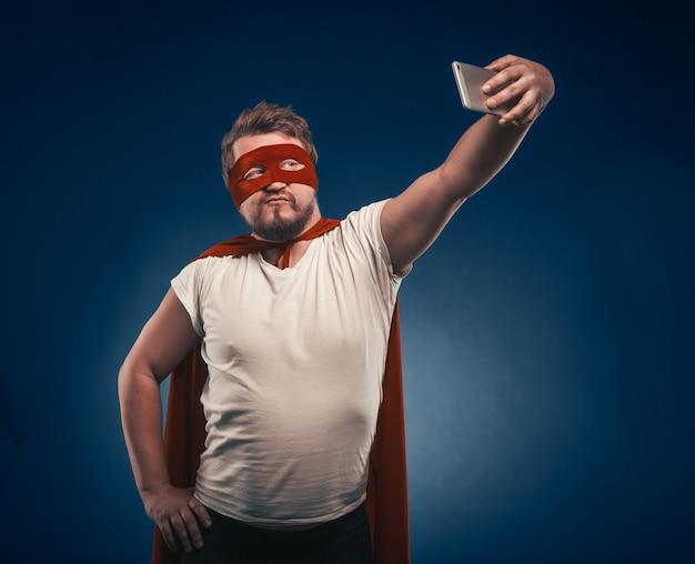 Narcistische superman neemt selfie door mobiele telefoons