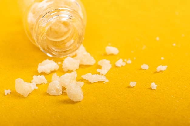 Narcotische zoutkristallen amfetamine op gele achtergrond.