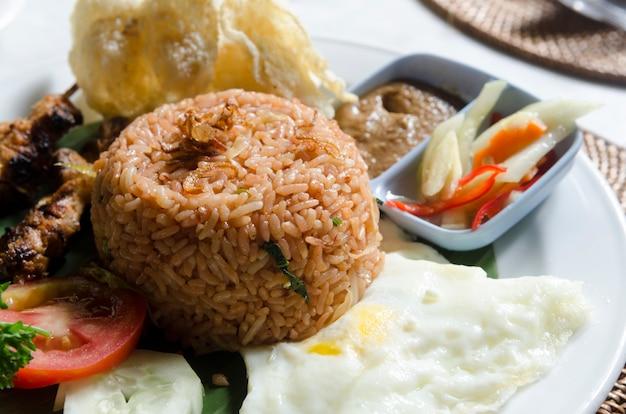 Nasi lemack stijl schotel verse groenten, noten en vis met rijst populair in indonesië