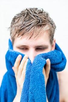 Nat mannenhaar en een handdoek vasthouden na het douchen thuis