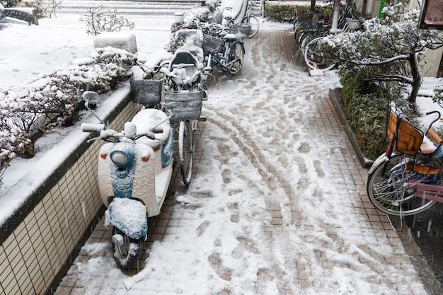 Nat sneeuwmengsel met afdrukken in de voortuin van een woongebouw