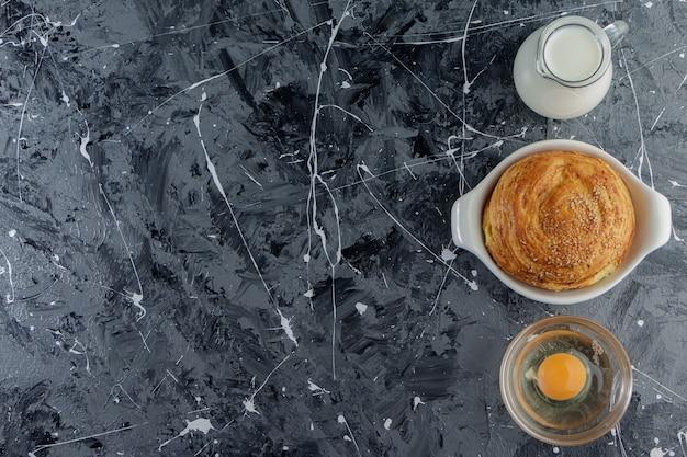 Nationaal gebakje van azerbeidzjan met ongekookt kippenei en een glazen kruik verse melk