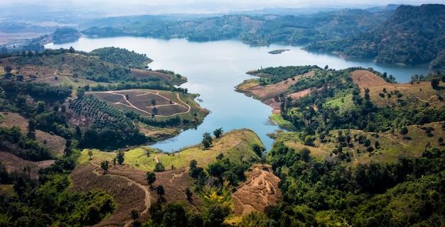 Nationaal reservoir of dam in het midden van de vallei en de weg die de stad verbindt in chiang rai thailand hoge hoekmening van drone-camera