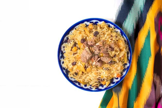 Nationaal voedsel - oezbeekse pilaf met vlees in plaat met traditioneel patroon, ikat-stof op witte houten tafel bovenaanzicht plat lag ramadan, concept van nowruz-vakantie