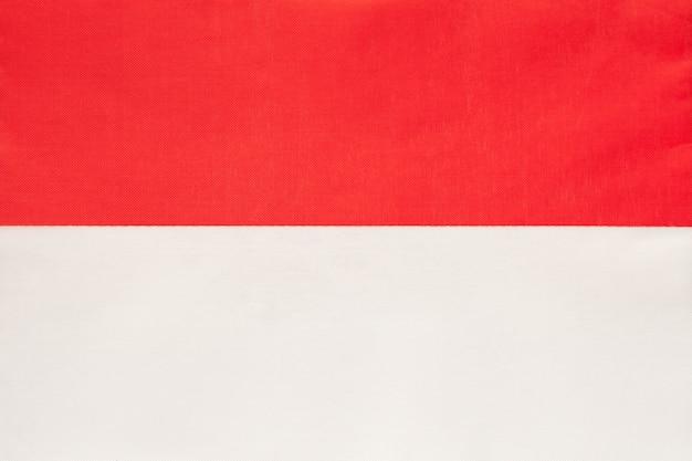 Nationale de stoffenvlag van monaco, textielachtergrond, symbool van het internationale europese land van de wereld,