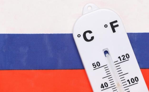 Nationale omgevingstemperatuurregeling. weerthermometer op achtergrond van russische vlag. opwarming van de aarde concept
