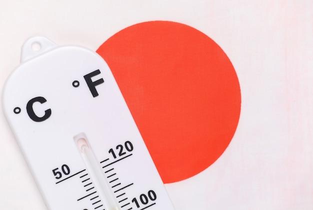 Nationale omgevingstemperatuurregeling. weerthermometer op de achtergrond van de japanse vlag. opwarming van de aarde concept