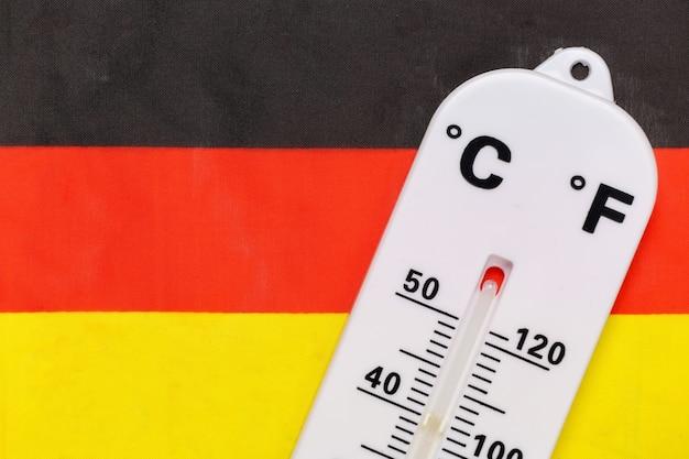 Nationale omgevingstemperatuurregeling. weerthermometer op de achtergrond van de vlag van duitsland. opwarming van de aarde concept
