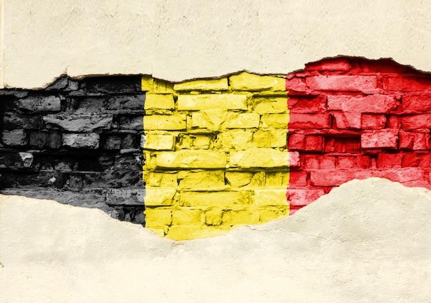 Nationale vlag van belgië op een bakstenen achtergrond. bakstenen muur met gedeeltelijk vernietigde pleister, achtergrond of textuur.