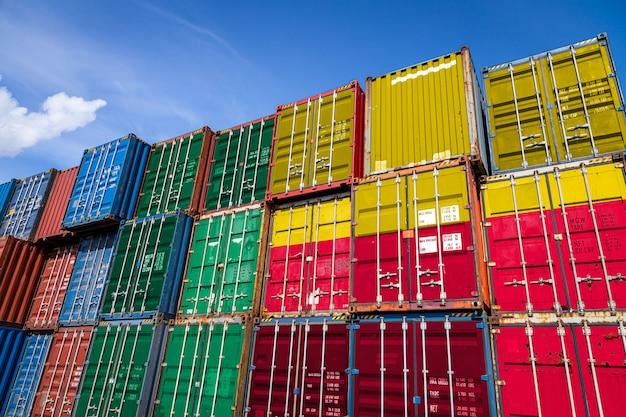 Nationale vlag van benin op een groot aantal metalen containers voor het opslaan van goederen gestapeld in rijen