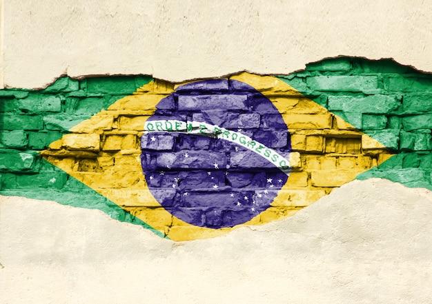 Nationale vlag van brazilia op een bakstenen achtergrond. bakstenen muur met gedeeltelijk vernietigde pleister, achtergrond of textuur.