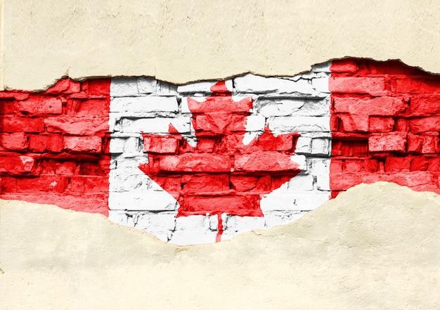Nationale vlag van canada op een bakstenen achtergrond. bakstenen muur met gedeeltelijk vernietigde pleister, achtergrond of textuur.
