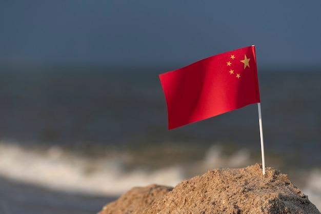 Nationale vlag van china op zeeoppervlak. vakantie in de volksrepubliek china op het strand.