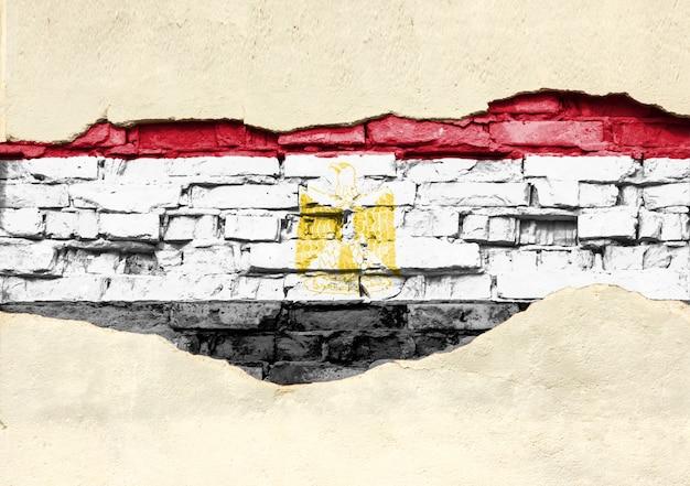 Nationale vlag van egypte op een bakstenen achtergrond. bakstenen muur met gedeeltelijk vernietigde pleister, achtergrond of textuur.