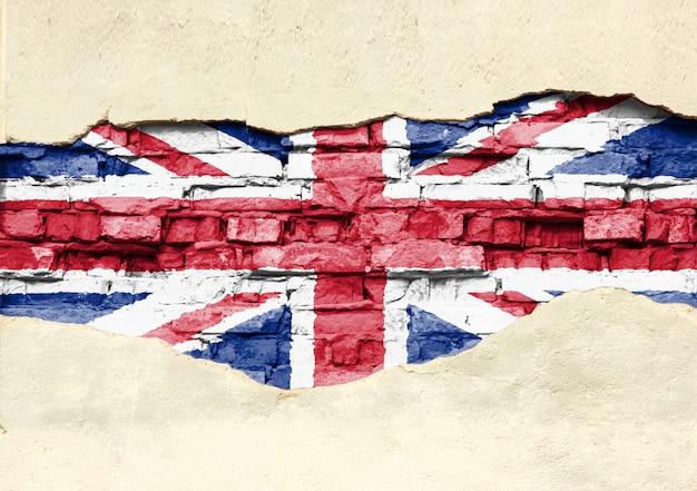 Nationale vlag van groot-brittannië op een bakstenen achtergrond. bakstenen muur met gedeeltelijk vernietigde pleister, achtergrond of textuur.