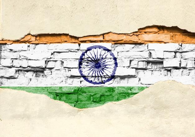 Nationale vlag van india op een bakstenen achtergrond. bakstenen muur met gedeeltelijk vernietigde pleister, achtergrond of textuur.