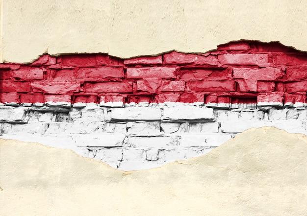 Nationale vlag van indonesië op een bakstenen achtergrond. bakstenen muur met gedeeltelijk vernietigde pleister, achtergrond of textuur.