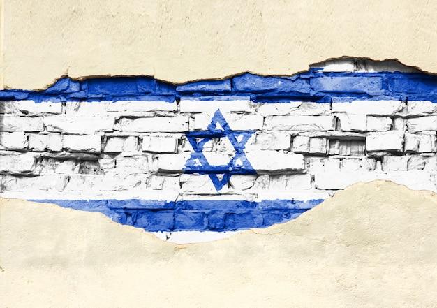 Nationale vlag van israël op een bakstenen achtergrond. bakstenen muur met gedeeltelijk vernietigde pleister, achtergrond of textuur.