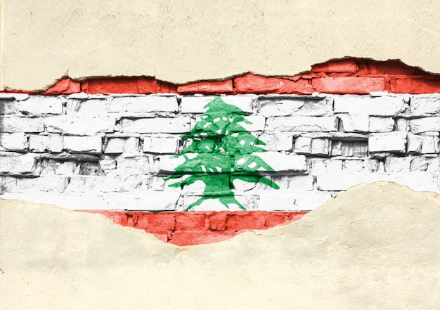 Nationale vlag van libanon op een bakstenen achtergrond. bakstenen muur met gedeeltelijk vernietigde pleister, achtergrond of textuur.