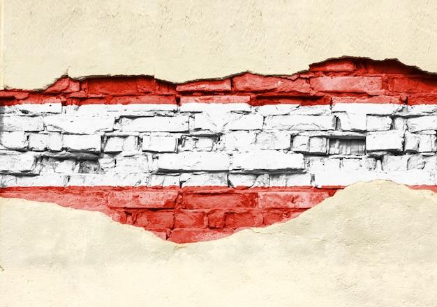 Nationale vlag van oostenrijk op een bakstenen achtergrond. bakstenen muur met gedeeltelijk vernietigde pleister, achtergrond of textuur.