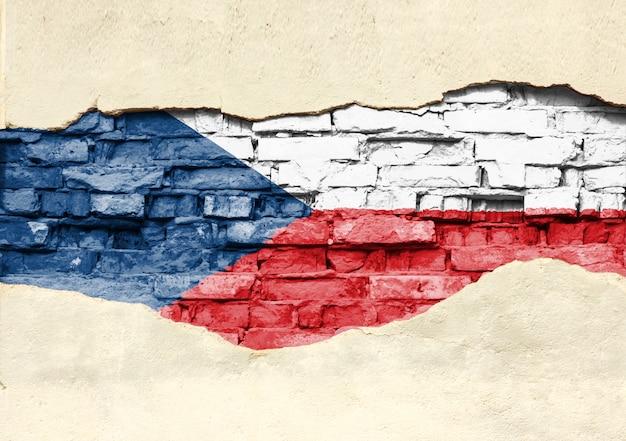 Nationale vlag van tsjechisch op een bakstenen achtergrond. bakstenen muur met gedeeltelijk vernietigde pleister, achtergrond of textuur.
