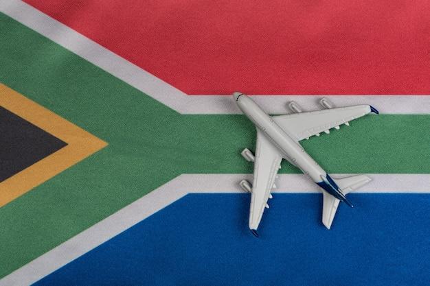 Nationale vlag van zuid-afrika en speelgoed vliegtuig close-up. hervatting van vluchten na quarantaine.