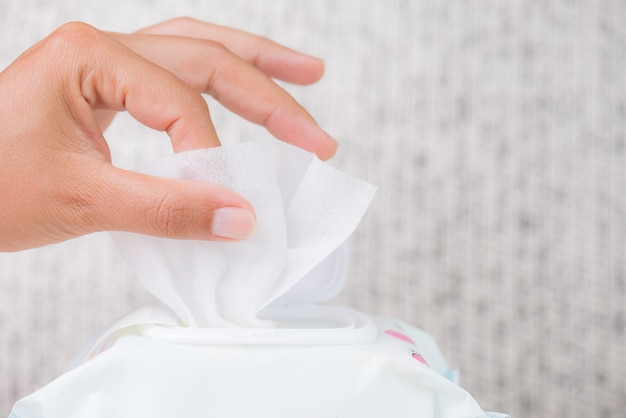Natte de hand van de vrouwenhand veegt van pakket af. gezondheidszorg concept.