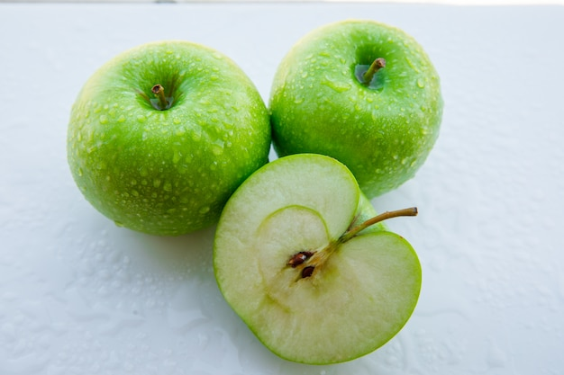 Natte groene appels en half op wit. detailopname.
