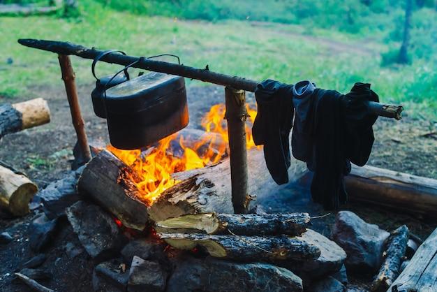 Natte kleding drogen op het kampvuur tijdens het kamperen, sokken drogen in brand