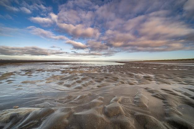 Natte kust met kleine plassen water onder een blauwe bewolkte hemel