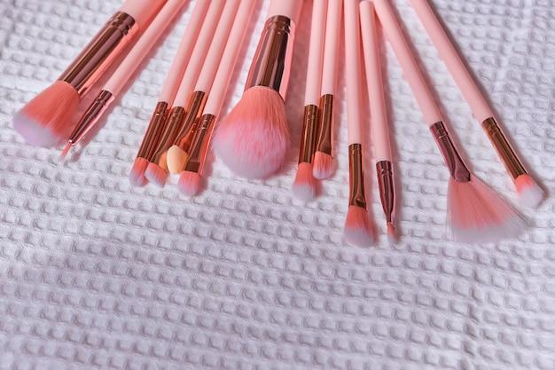 Natte make-upborstels op een witte wafelhanddoek na het reinigen